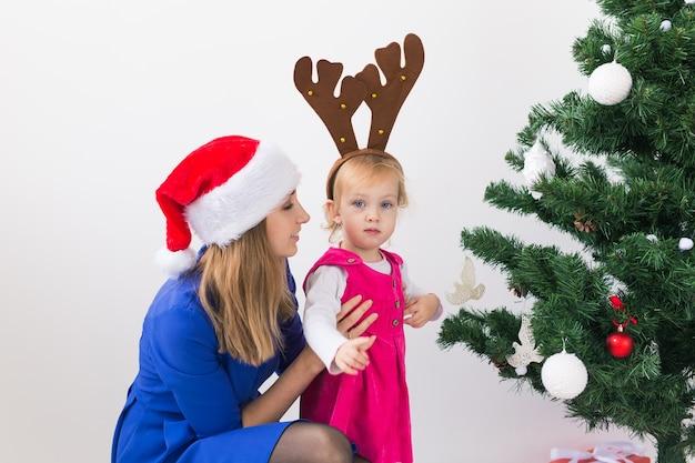 Mutter und ihre kleine tochter neben dem weihnachtsbaum