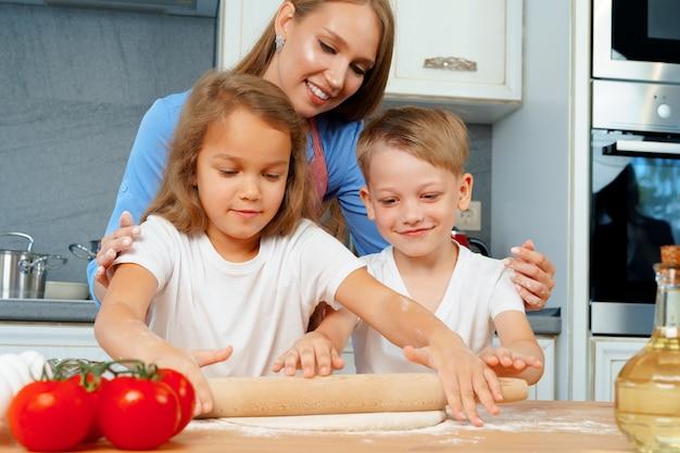 Mutter und ihre kleinen kinder, jungen und mädchen, helfen ihr, teig zuzubereiten