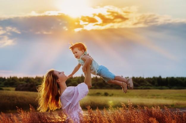 Mutter und ihre tochter bei sonnenuntergang