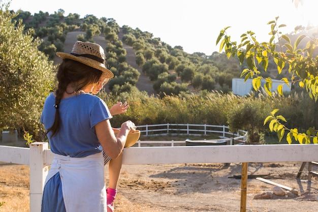 Mutter und ihre tochter, die nahe dem zaun steht im olivgrünen obstgarten steht