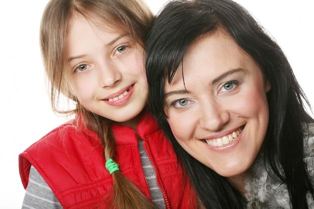 Mutter und ihre tochter lächeln in die kamera