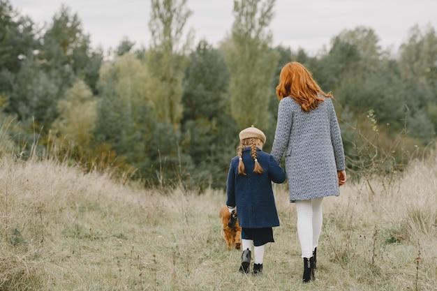 Mutter und ihre tochter spielen mit hund. familie im herbstpark. haustier-, haustier- und lebensstilkonzept. herbstzeit.