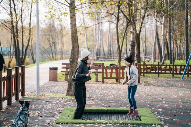 Mutter und ihre tochter springen zusammen auf trampolin im herbstpark