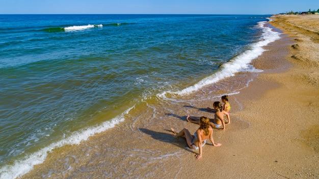 Mutter und ihre töchter genießen den meerblick, während sie in den wellen am meer sitzen