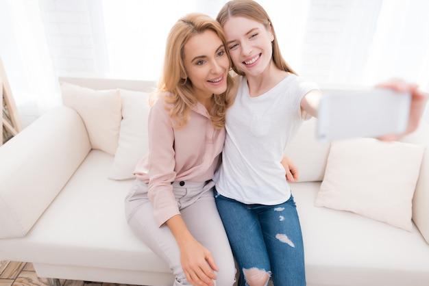 Mutter und jugendliche tochter, die selfie auf sofa nehmen.