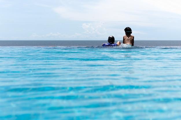 Mutter und junger sohn entspannen sich im swimmingpool, der über dem ozean auf sommerferien schaut.