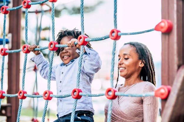 Mutter und junges kind, sohn, afrikanische schwarze rasse, spielen zusammen im spielplatzpark, haben spaß und genießen die freizeitaktivitäten im freien