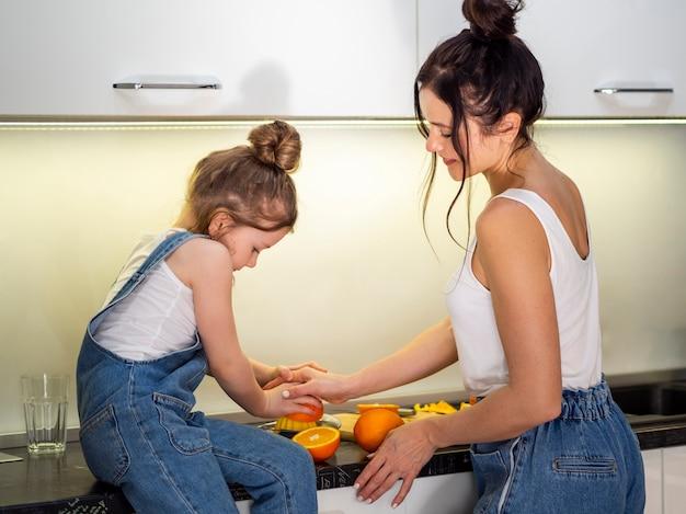 Mutter und junges mädchen bereiten orangensaft vor