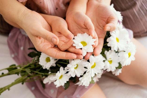 Mutter und junges mädchen halten strauß der frühlingsblumen