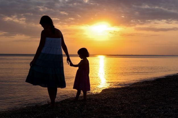 Mutter und kind am sonnenuntergangsstrand