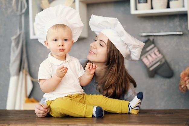 Mutter und kind auf küche, weiße hüte des chefs, verhältnisse der mutter und des sohns