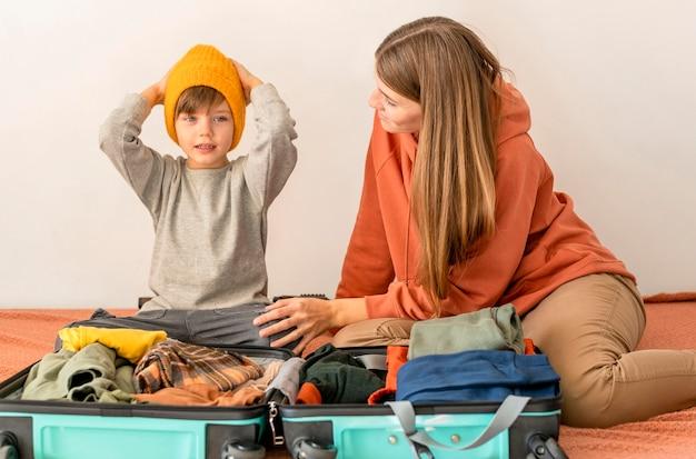 Mutter und kind bereiten gepäck für die reise vor