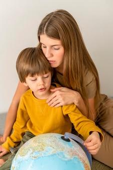 Mutter und kind betrachten globus zusammen