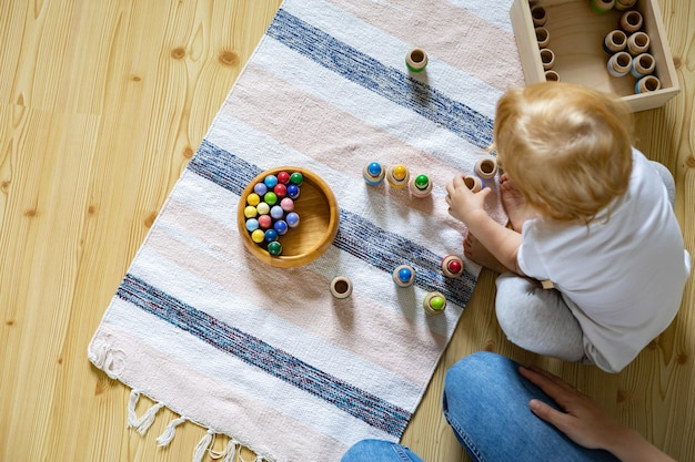 Mutter und kind, die lernspielzwerge in fässern spielen, verwenden die entwicklung der maria-montessori-methode