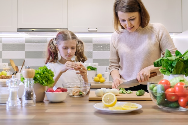 Mutter und kind, die zusammen zu hause in der küche kochen