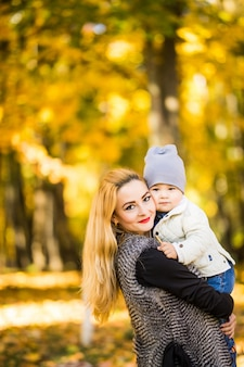 Mutter und kind gehen in den goldenen herbstpark