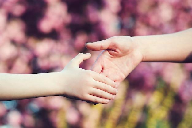 Mutter und kind hände auf naturhintergrund familienunterstützung hilfe und vertrauen eltern halten die hand