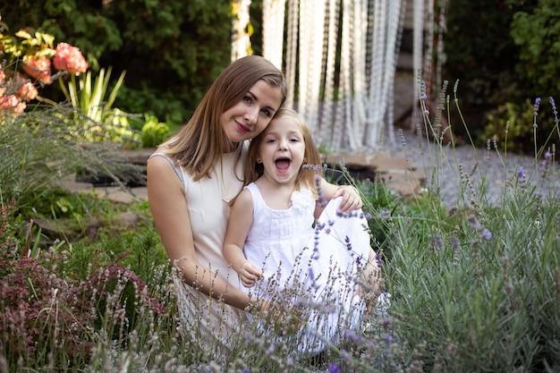 Mutter und kind im lavendel umarmen sich und haben spaß im freien in der natur