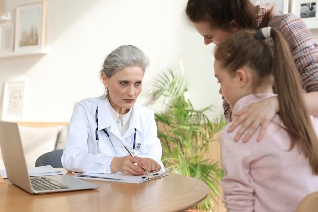 Mutter und kind in der arztpraxis treffen den kinderarzt, sie sitzen am schreibtisch im krankenhaus.
