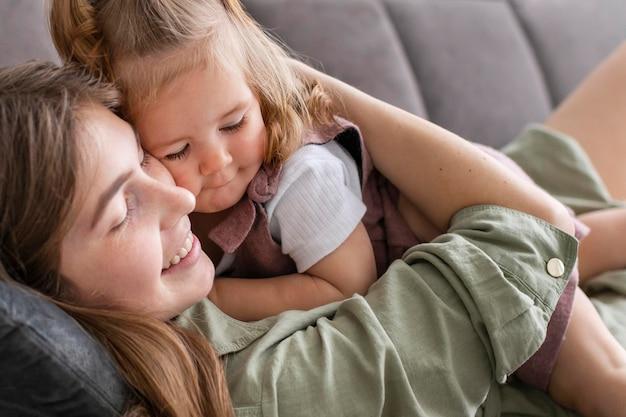 Mutter und kind liegen auf der couch
