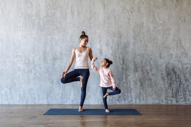 Mutter und kind machen zusammen yoga auf der matte .familiensport