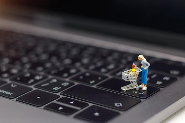 Mutter und kind mit der einkaufskarte, die auf laptoptastatur steht.