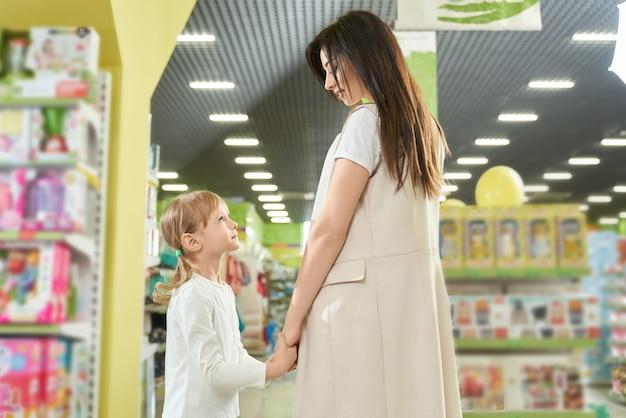 Mutter und kind posieren, händchen haltend im spielzeugladen.