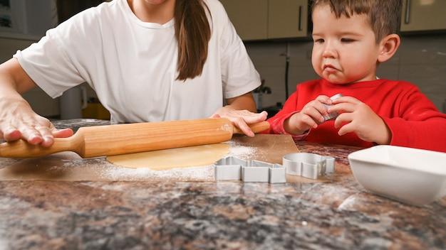 Mutter und kind rollen den teig für kekse