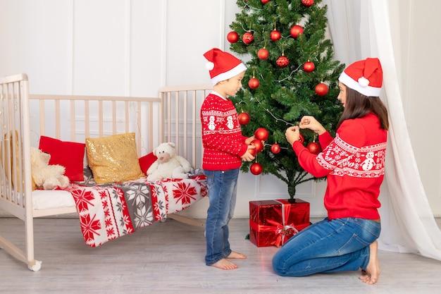 Mutter und kind schmücken den weihnachtsbaum
