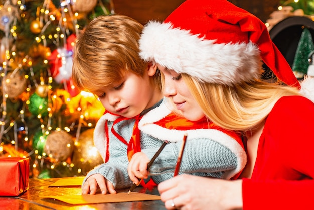 Mutter und kind schreiben einen brief an den weihnachtsmann in der nähe des weihnachtsbaumes