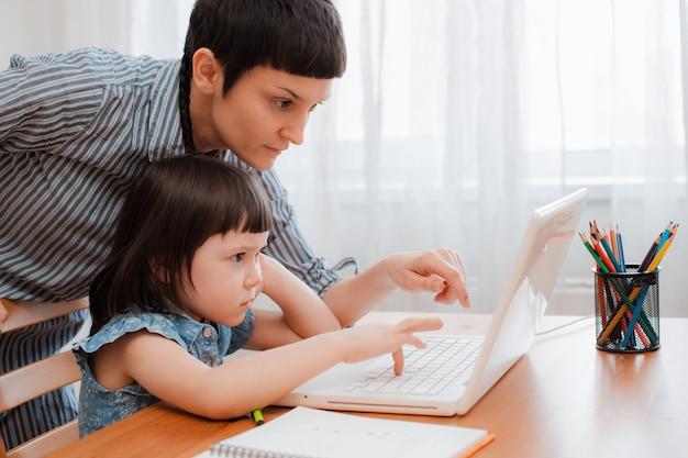 Mutter und kind schüler zu hause auf einem laptop lernen hausaufgaben. e-home-schule während der zeit der pandemie und des coronavirus. elternhilfeschulung.