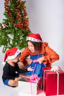 Mutter und kind sehr glücklich mit geschenk ein tagweihnachten und ein guten rutsch ins neue jahr auf hintergrund im studio