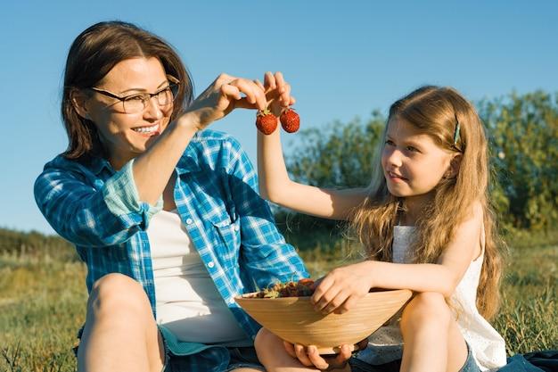 Mutter und kind sitzen auf dem rasen und essen erdbeeren.