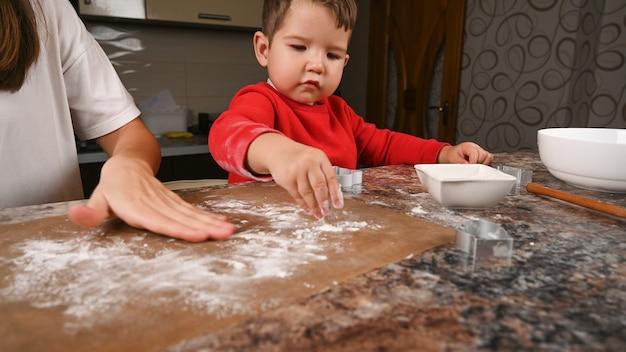 Mutter und kind streuen mehl auf die backmatte