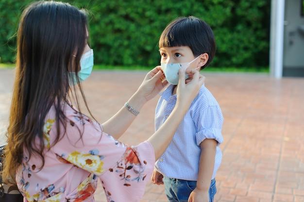 Mutter und kind tragen während des ausbruchs des covid-19-virus und der grippe eine gesichtsmaske.