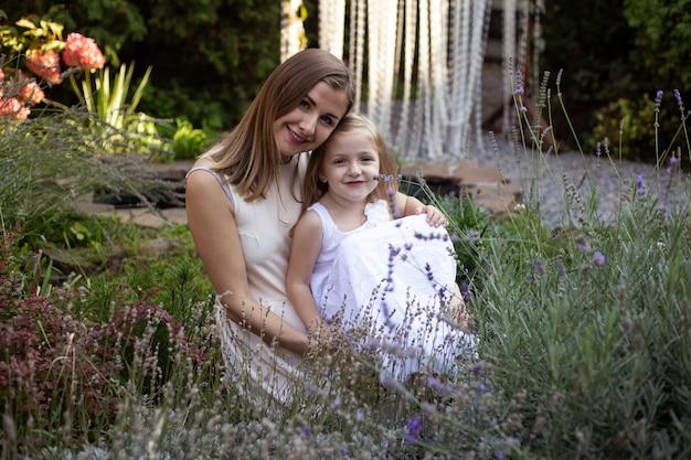 Mutter und kind umarmen sich und haben spaß im freien in der natur in lavendel