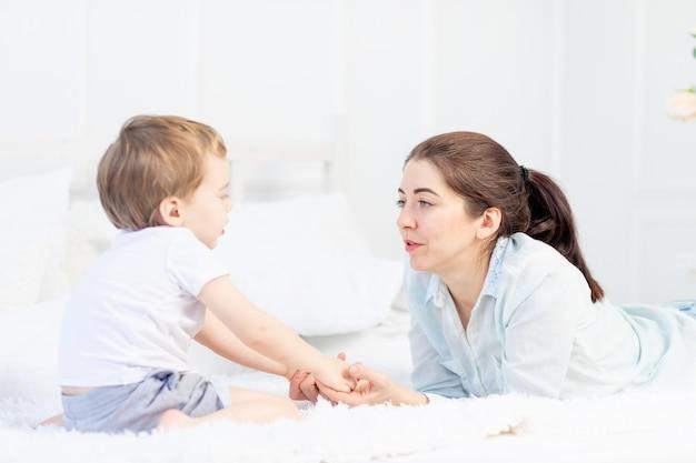 Mutter und kind unterhalten sich zu hause auf dem bett, das konzept der beziehung zwischen eltern und kindern