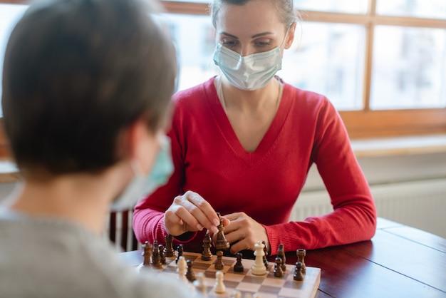 Mutter und kind während der coronavirus-krise spielen zu hause schach