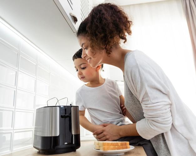 Mutter und kind warten auf toastbrot