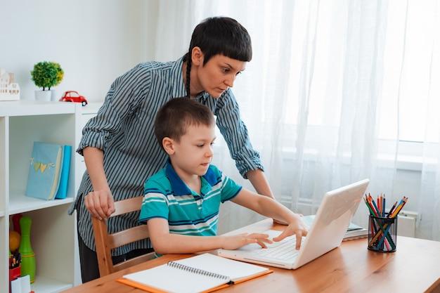 Mutter und kind zu hause mit einem laptop, lernen