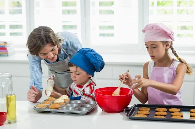 Mutter und kinder bereiten kekse in der küche vor