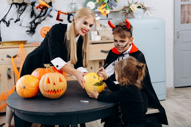 Mutter und kinder, die auf kürbis zeichnen, spielen und haben lustige zeit zu hause. halloween
