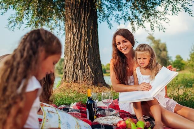 Mutter und kinder, die draußen bücher lesen. familie, die picknick im park bei sonnenuntergang hat.
