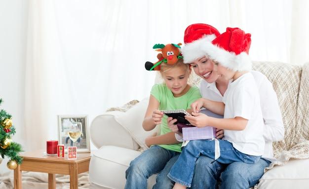 Mutter und kinder, die einen kalender sitzt auf dem sofa betrachten