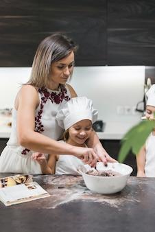 Mutter und kinder, die teig auf unordentlicher küchentheke vorbereiten