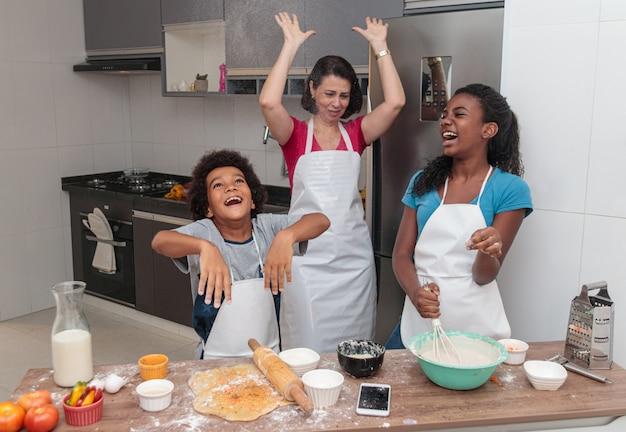 Mutter und kinder, die zusammen das mittagessen in der küche vorbereiten