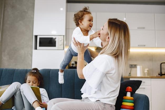 Mutter und kinder entspannen sich gemeinsam auf dem sofa zu hause im wohnzimmer. kleine mädchen, die mit spielzeug spielen und ein buch lesen.