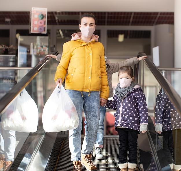 Mutter und kinder gehen mit masken während der quarantäne einen bagger in einem einkaufszentrum hinunter.