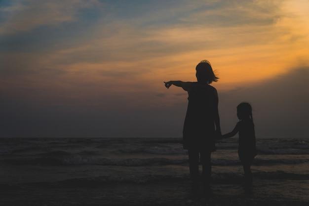 Mutter und kinder gehen und läuft am meer bei sonnenuntergang