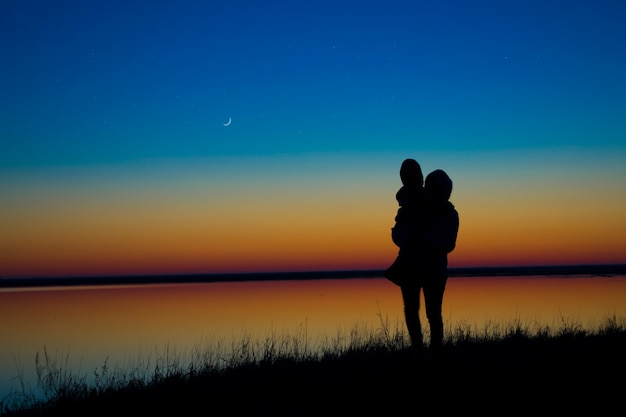 Mutter und kinder halten händchen im hintergrund des sonnenuntergangs